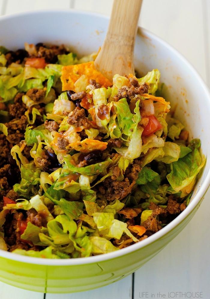 salade romaine, cuillère en bois, bol blanc, lentilles, salade composée originale, plusieurs ingrédients
