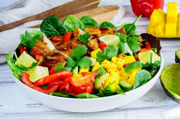 salade verte, poivres rouges, mangues, citrons découpés, salade aux épinards originale