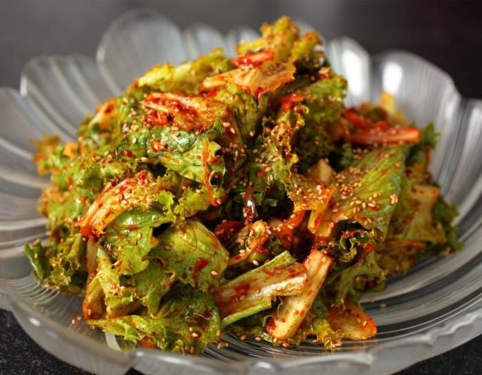salade aux graines de sésame et à la sauce rouge placé dans un grand bol en verre