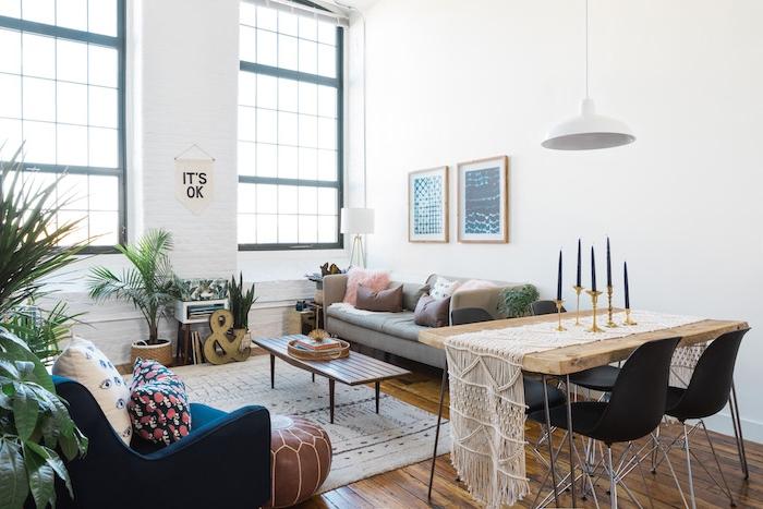 design loft dans un grand studio avec grandes fen6etres, table rustique avec chaises noires, canapé gris décoré de coussins décoratifs, fauteuil bleu, pour marron