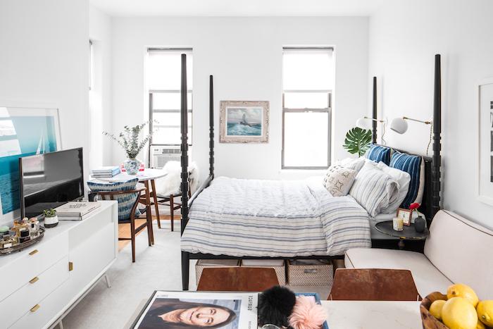 lit vintage bois marron, meuble tv blanc, table et chaises bois, murs blancs, ambiance artistique dans appartement petit