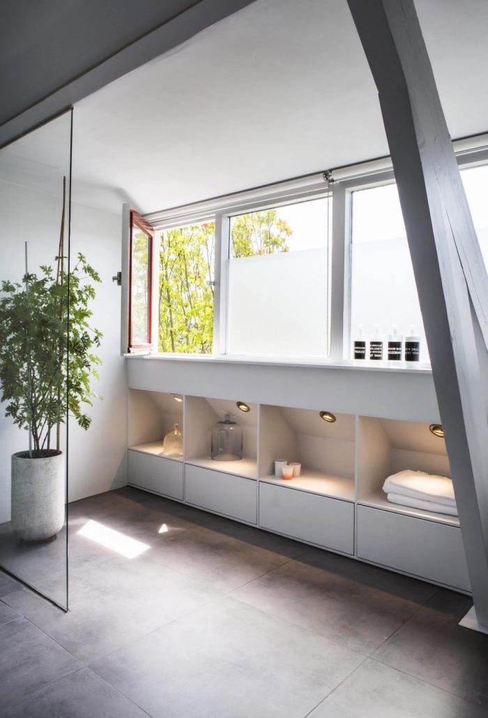 une salle de bains au design moderne avec meuble sous pente intégré au soubassement offrant un espace de rangement supplémentaire