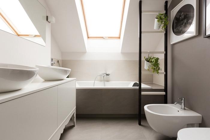 petite salle de bains aménagée dans les combles avec baignoire posée dans l'espace le plus bas sous le toit