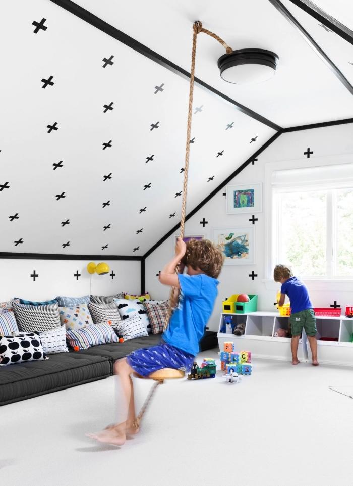 une salle de jeu noir et blanc aménagée sous les combles avec un matelas de sol cocooning posé sous la pente du toit