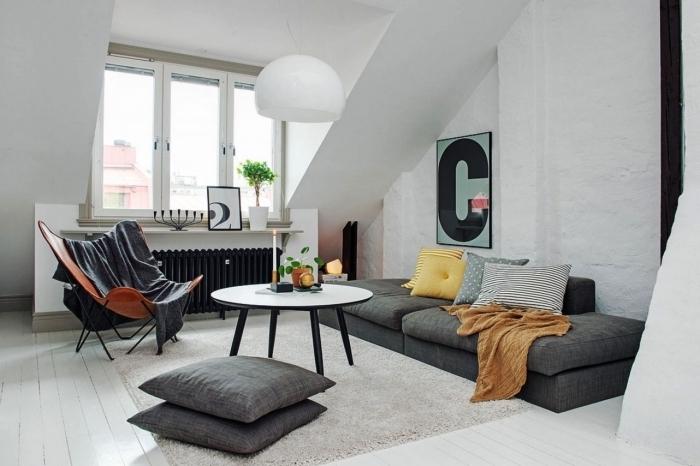 une chambre sous comble au design moderne scandinave avec canapé au ras du sol posé sous la pente