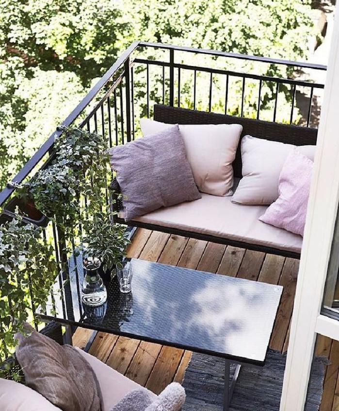 deco de reve, aménagement petit balcon avec des sièges décorés de coussins rose et table basse design couleur noire, revetement terrasse bois