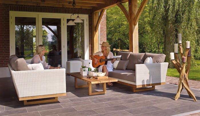 salon de jardin en rotin avec table basse en bois et grands canapés extérieurs en résine tressée et bois sur terrasse extérieure abritée sous pergola bois