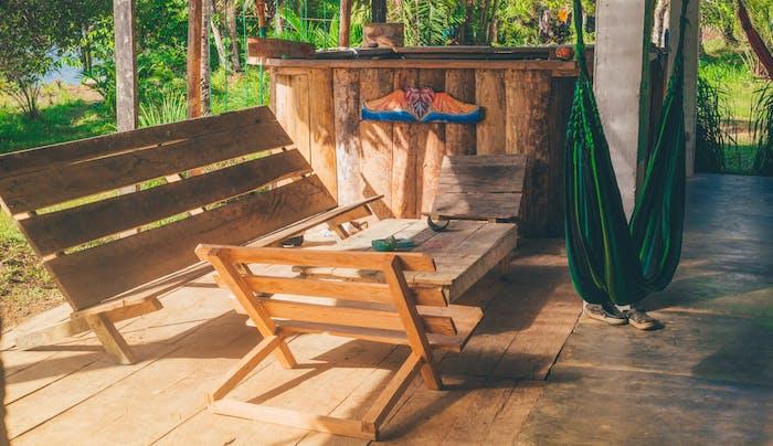 comment faire un salon de jardin soi meme en bois brut sur une terrasse en bois, banc, chaises et table bois brut, balancelle hamac style boheme chic