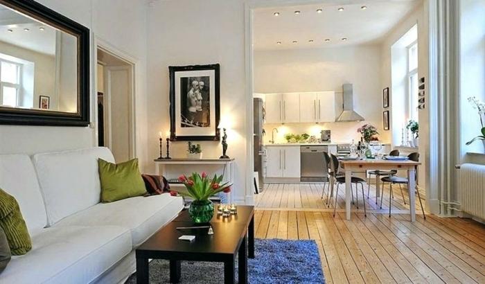 studio spacieux avec coin cuisine, table de repas, tapis bleu, table de salon noire, sofa blanc, tableau photo monochrome