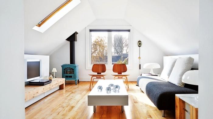 meuble sous pente bas en bois naturel qui accueille le tv dans ce petit salon mansardée au design épuré