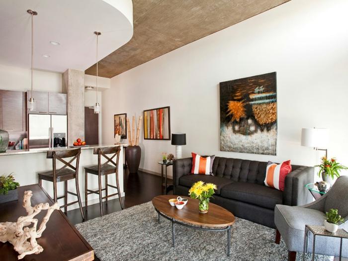 appartement moderne avec cuisine équipée donant sur le séjour, table ovale en bois, sofa gris