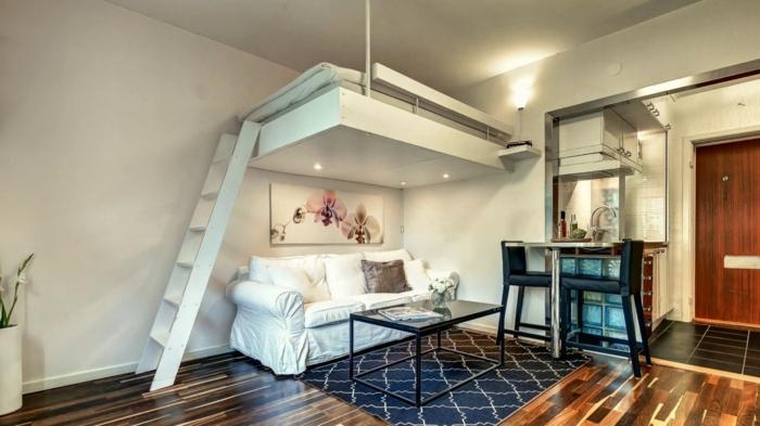 appartement avec cuisine et lit flottant, tapis bleu géométrique, mini cuisine équipée