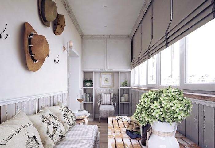 modele de deco terrasse couverte balcon avec table en palette recyclée, canapé en palette décoré de coussins gris, deco murale de chapeaux, stores d interieur, interieur deco champagne chic