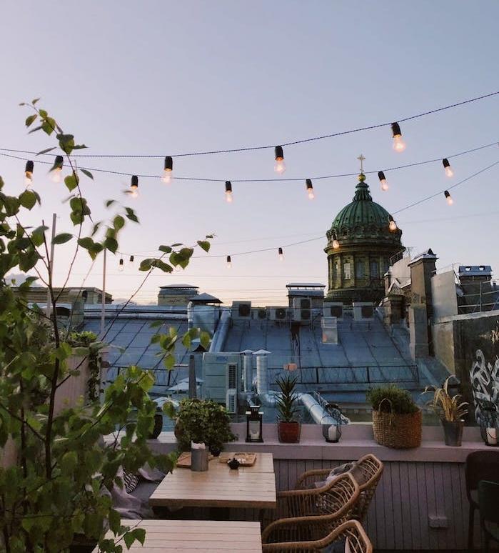ambiance romantique sur un balcon cocooning avec des tables et chaises en bois, guirlande d ampoules electriques, plantes vertes en pots de fleurs