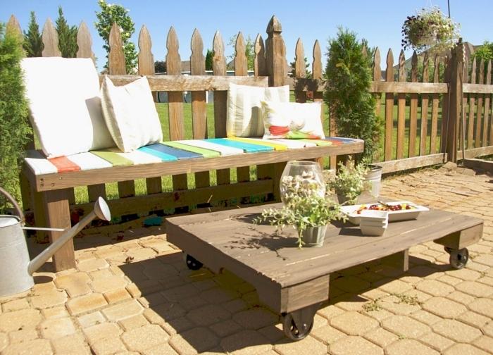 modèle de canape exterieur en palette décoré avec peinture différentes couleurs et coussins blancs, idée déco terrasse ou jardin
