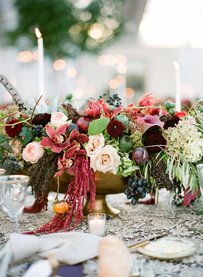 grand bol métallique, bougies blanches, orchidées, roses et fruits, nappe en macramé blanc