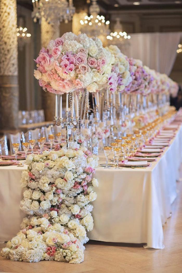 longue table élégante, plafonniers en cristal, grand chemin de fleurs verres aux rebords dorés