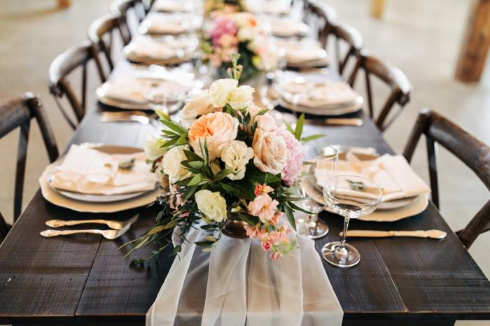 table de mariage en bois foncé, assiettes couleur ivoire, chemin de table en tulle blanc
