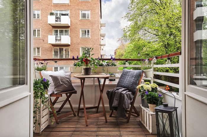 aménagement petit balcon avec vue, table ronde basse et chaises de bois sur balcon avec revetement sol bois, coussins gros et plaid, pots de fleurs fleuries