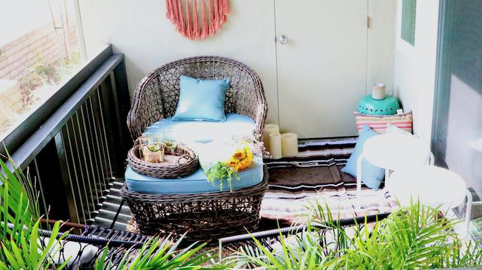 table et fauteuil tressé sur un balcon avec tapis marron, plantes exotiques, decoration balcon style oriental