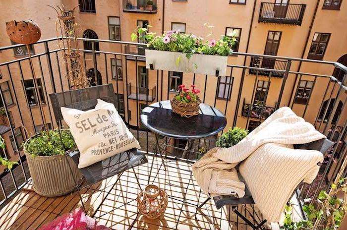balcon en bois avec garde corps metal, chaises et table minimalistes, coussin et plaid beige, bacs et pots de fleurs pour un balcon bien fleuri