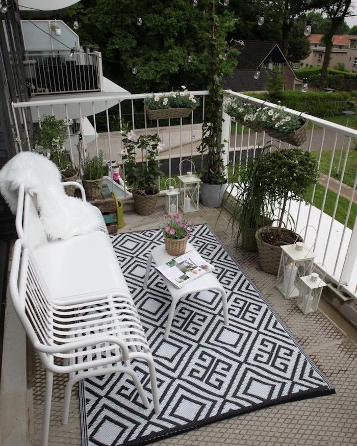 deco scandinave nordique sur un balcon avec banc en metal blanc et table blanche minimaliste sur tapis noir et blanc, plantes en po, lanternes blanches decoratives