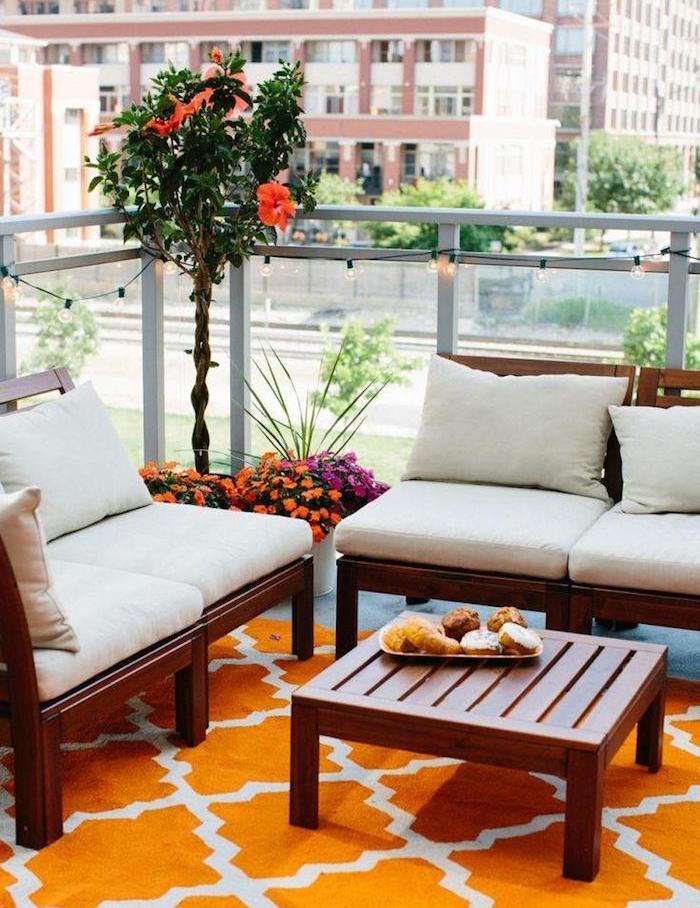 salon de balcon coloré avec canapés en bois et table bois sur tapis orange, fleurs en pots et guirlande lumineuse originale