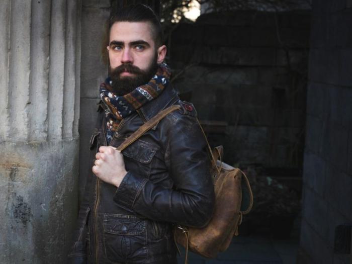 veste en cuir, écharpe aux motifs ethniques, sac à dos en cuir marron, homme barbu, cheveux en arrière