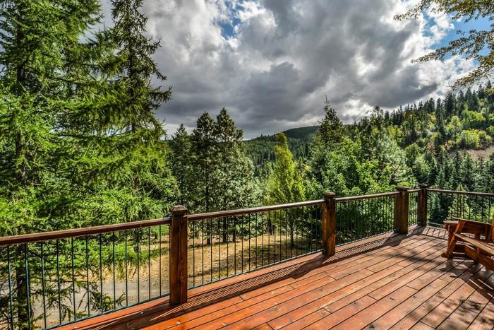 extérieur de chalet de montagne, sapins verts, ciel aux nuages blancs, terrasse en bois exotique