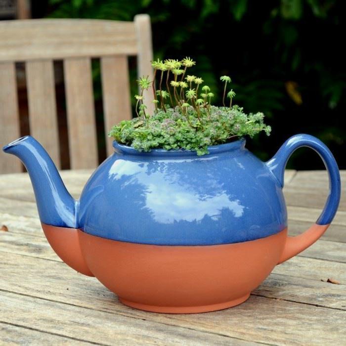 théière bicolore, herbe verte, idée déco jardin avec théière, table en bois, chaise en bois
