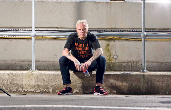 photo de keith flint assis sur un trottoir en tenue casual pour article d'actualités sur les causes révélées de sa mort par pendaison