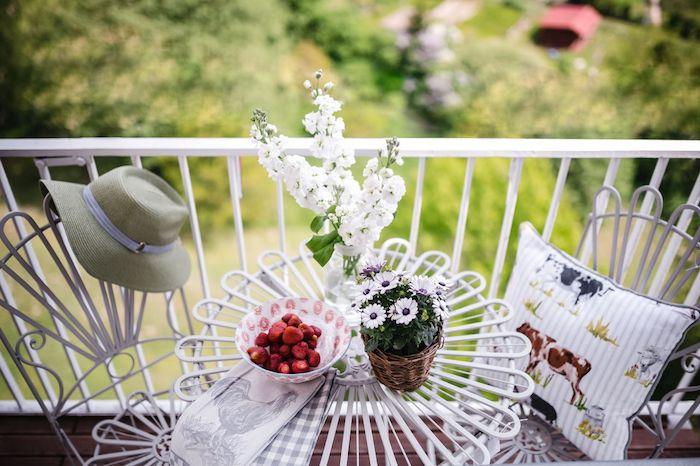table et chaises blanches en metal sur un tout petit balcon avec decoration fleurie, ambiance relaxante et cosy