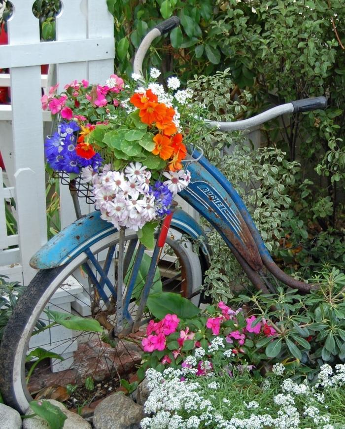 verdure abondante et bicyclette bleue, pots de fleurs sur la corbeille du vélo, déco jardin fleurie vintage