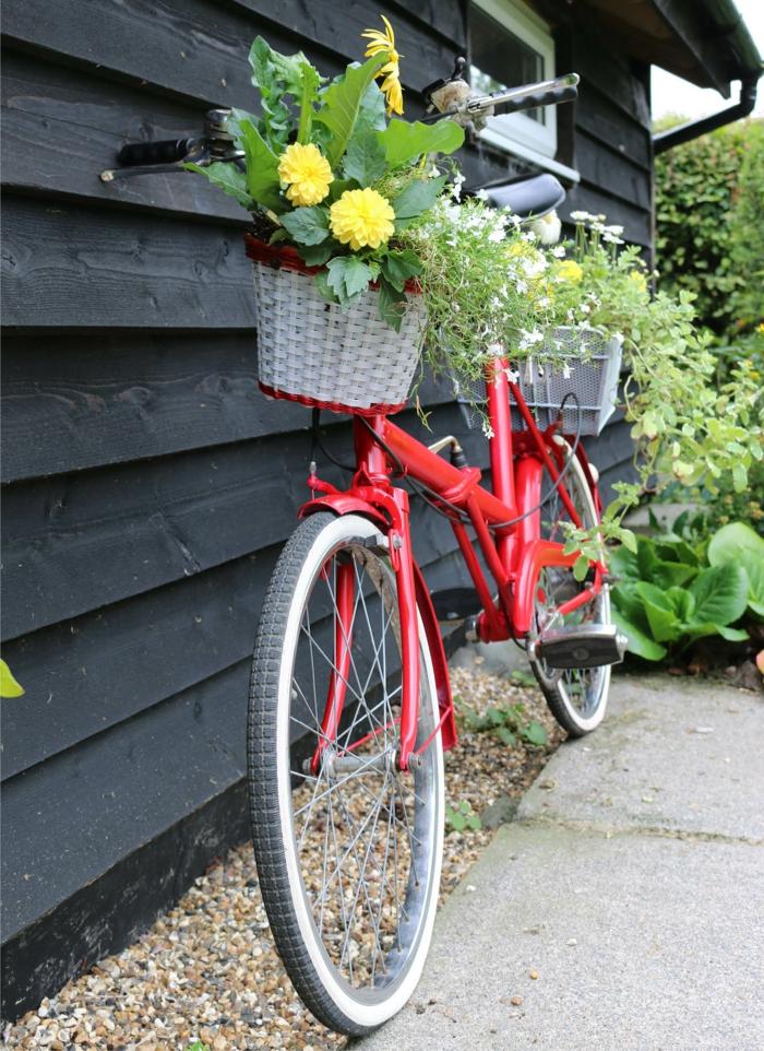 vélo vintage rouge utilisé comme support pour pots de fleurs, maisonnette en bois, decor jardin créatif