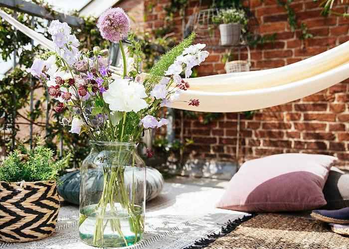 ambiance campagne chic sur un balcon avec tapis et coussins et poufs par sol et hamac exterieur, plusieurs plantes en pots