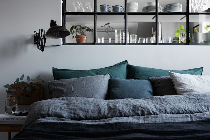 photo d'une verrière intérieur atelier avec carreaux carrés et cadre noir aluminium incrustée dans mur blanc séparant cuisine et salon
