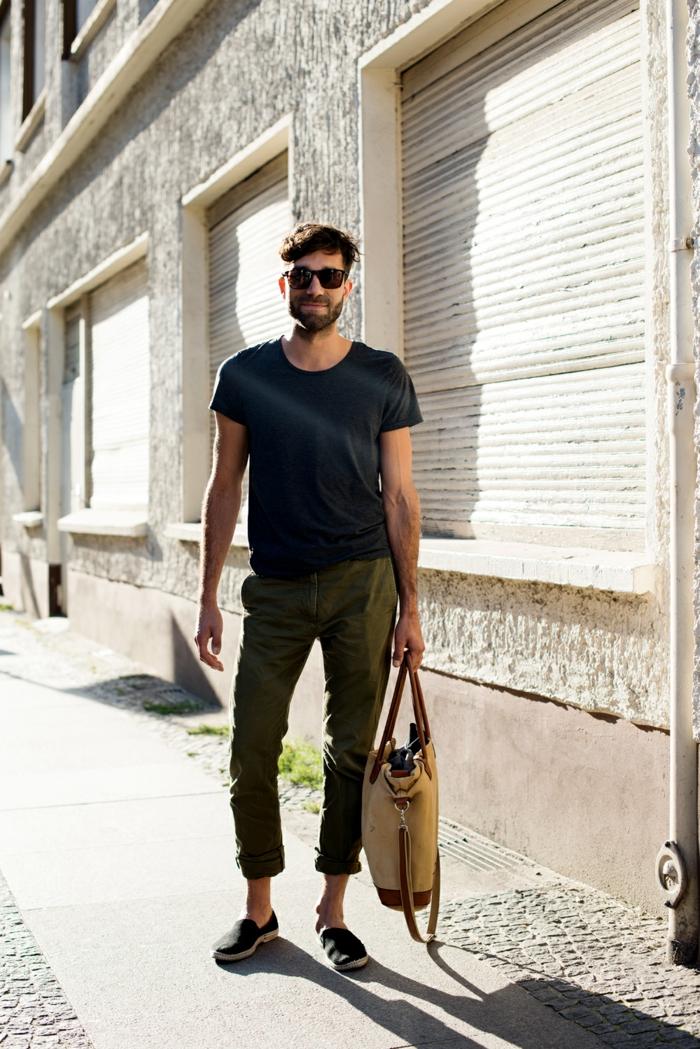 pantalon vert militaire, shirt noir, gros sac beige, lunettes de soleil, espadrilles, mode hippie homme