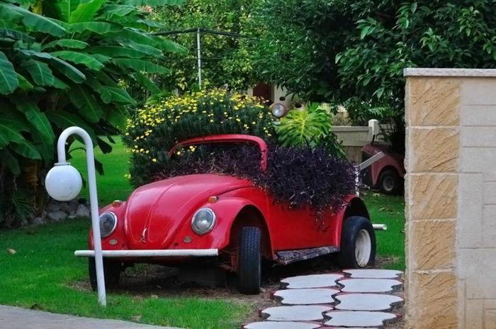 deco exterieur pour un grand jardin, lampes de jardin, pelouse verte, ancienne voiture rouge avec fleurs plantées