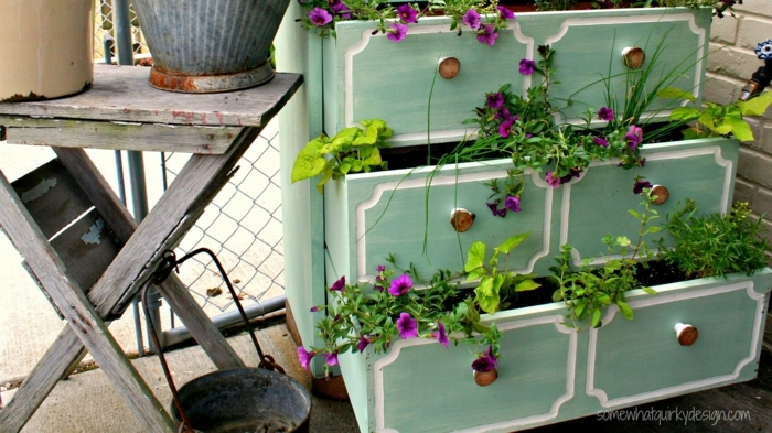 commode avec placards bleus aux poignées métalliques, tiroirs transformés en jardinières