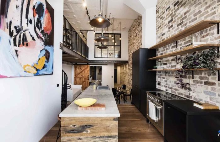 exemple de deco murale industrielle avec briques, meuble de rangement étagères en bois, modèle de cuisine avec îlot