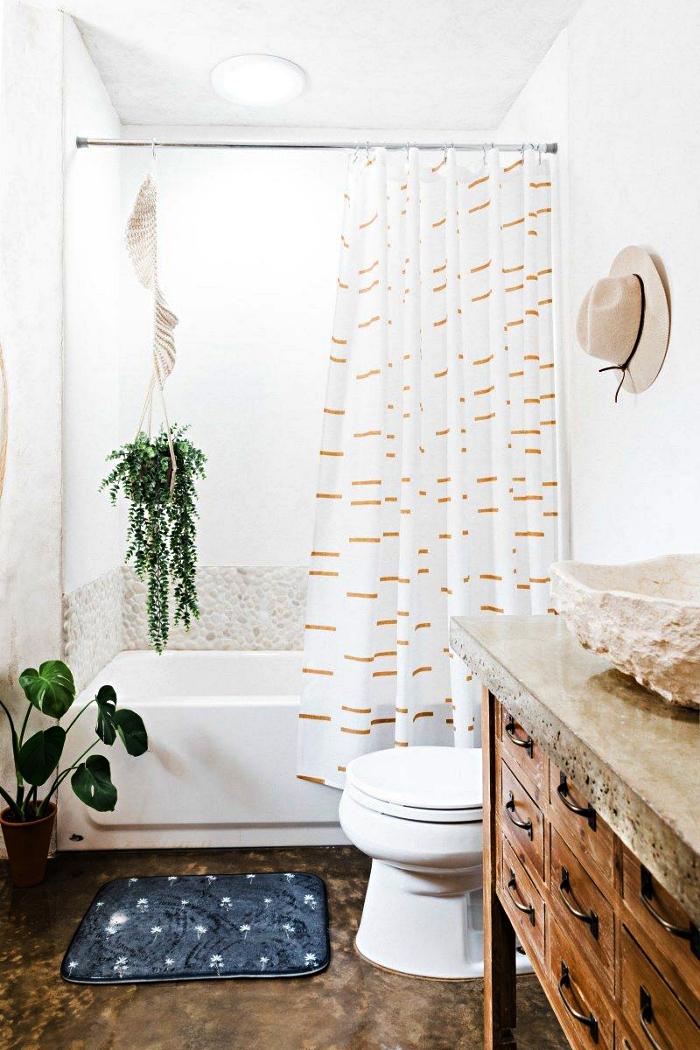 idée d'aménagement d'une petite salle de bain de 5m2 dans un style nature, baignoire-douce avec crédence en galets décorée d'une plante suspendue, meuble sous vasque chiné avec une vasque à poser en pierre naturelle