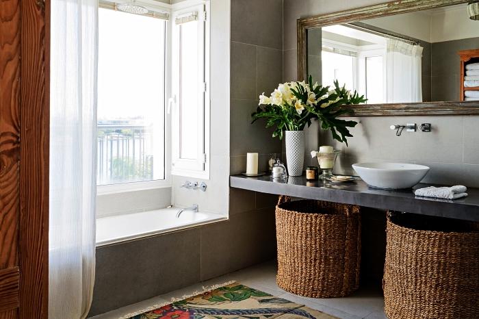 salle de bain nature et rustique avec plan vasque en béton, une vasque à poser ovale et de gros paniers en fibres naturelles