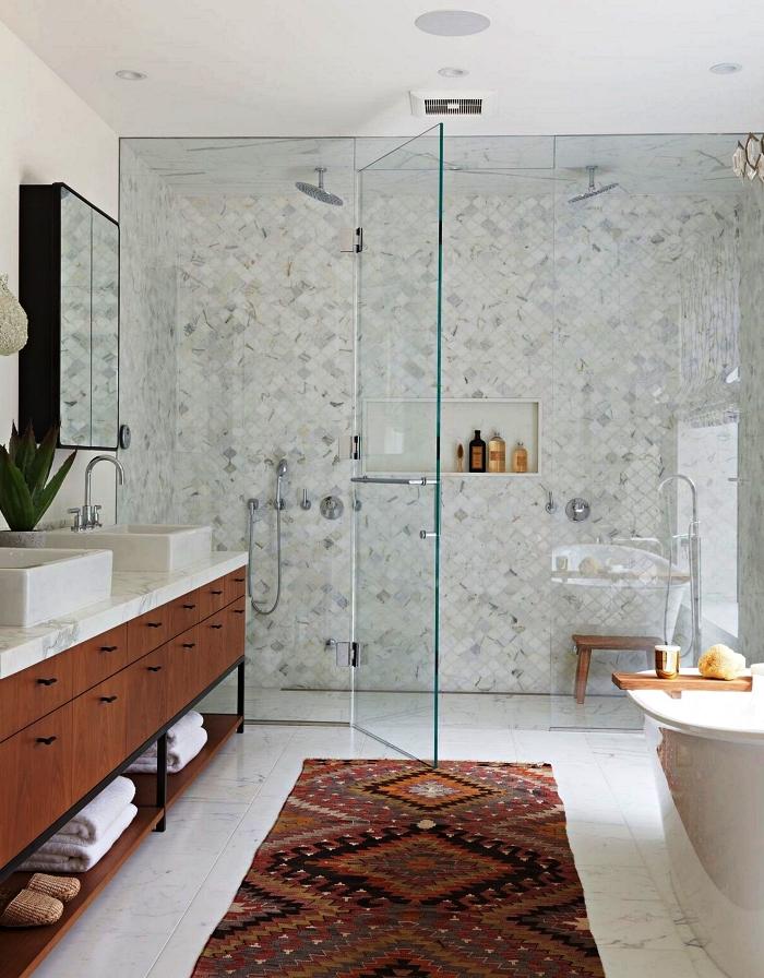 salle de bain blanche et bois avec douche italienne en petits carreaux posés à la diagonale, un tapis graphique ethnique qui s'harmonise avec le meuble sous vasque vintage