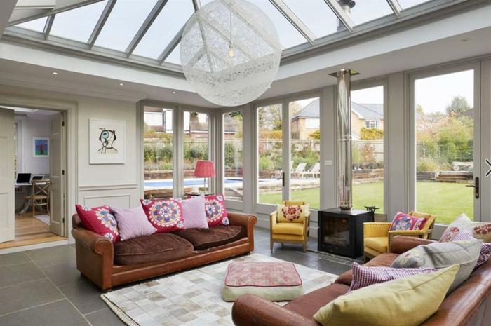 construire une veranda contemporaine, sofas marron et plueurs coussins, tapis blanc, toiture en fenêtres