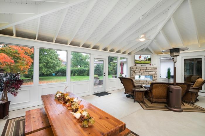 amenagement de véranda spacieuse et blanche, grande table en bois, salon et salle à manger