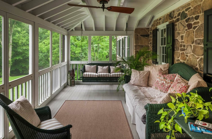 aménagement de véranda comme coin de relaxation, chaises en rotin, coussins, parement pierre
