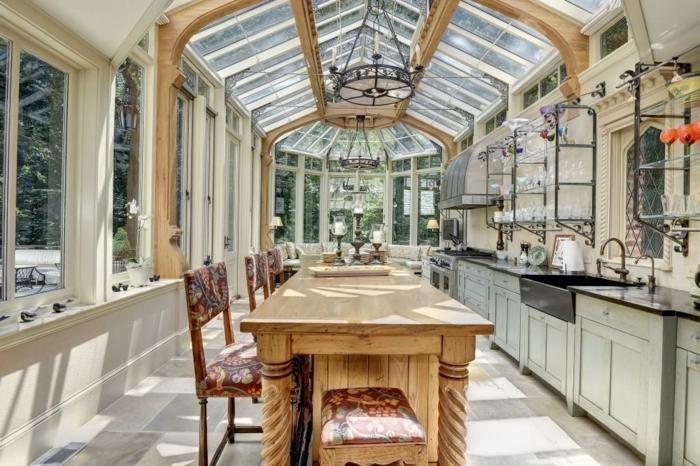 amenagement interieur de veranda, table en bois clair, toiture vitrée, placards blancs, cuisine dans veranda
