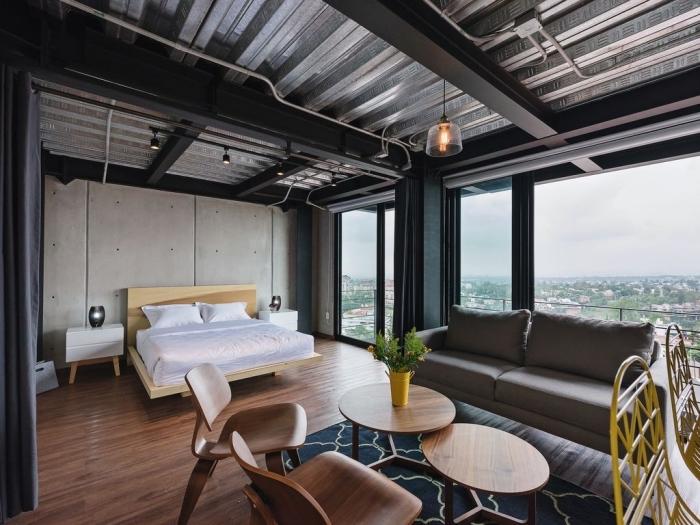 exemple de chambre à coucher dans un studio moderne, modèle de plafond avec poutres apparentes en noir