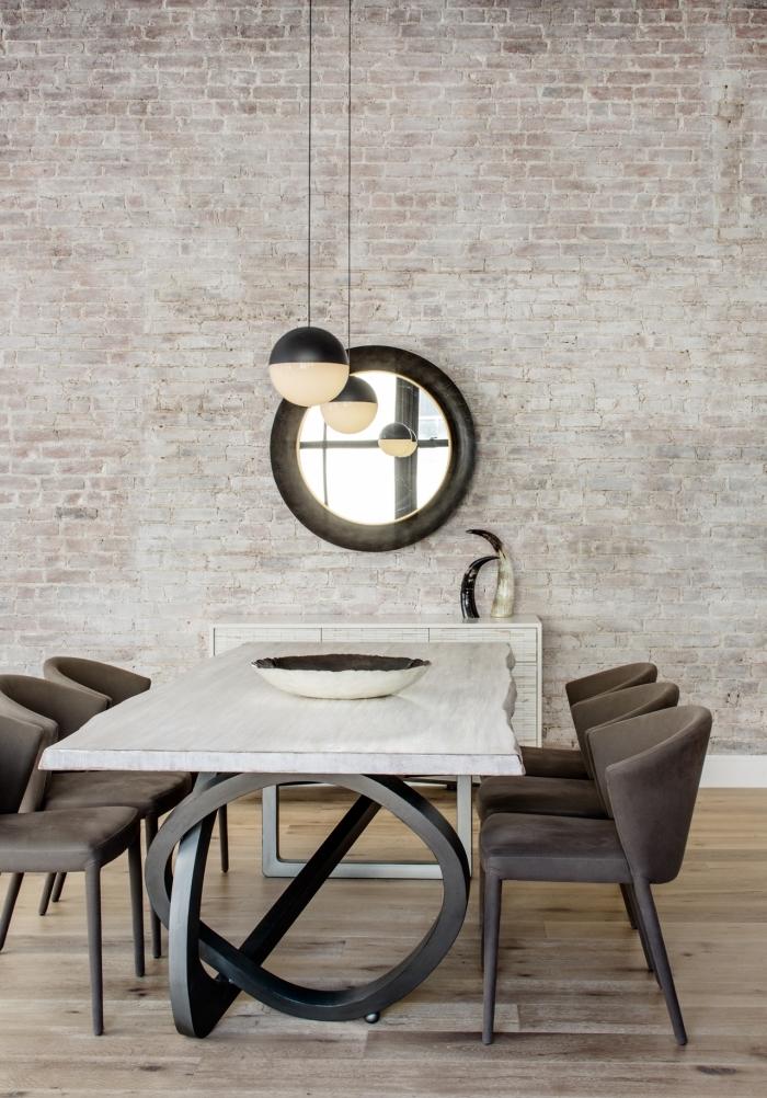 pièce aux murs briques avec plancher bois clair, idée déco salle à manger ouverte vers une cuisine industrielle
