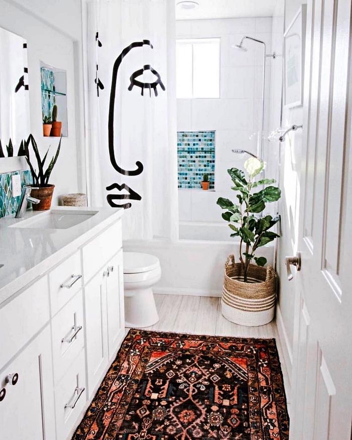 salle de bain blanche avec rideau au design original de visage femme, décorée de touches de mosaïque bleue et de quelques plantes vertes